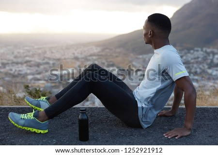 Photo of relaxed man with short hair, dark skin, sits on highway with bottle of cold water, wears tracksuit, focused aside, enjoys spare time, mountain view, rests after workout. Fitness, exercising #1252921912