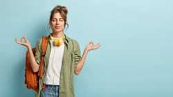 Photo of relaxed student keeps hands in mudra gesture, keeps eyes closed, listens peaceful music, headphones on neck, wears shirt and jeans, has rucksack, isolated on blue background with free space