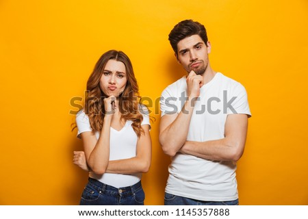 Photo of resented man and woman in casual clothes standing together and touching chin with irritated look isolated over yellow background
