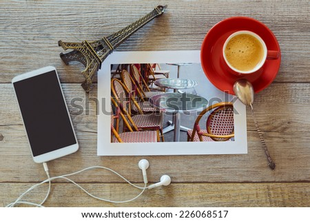 Photo of restaurant in Paris on wooden table with coffee cup and smart phone. View from above