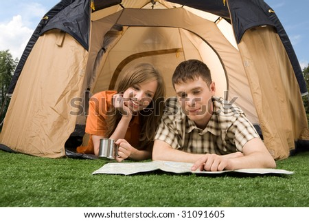 Photo of resting couple lying on green grass in tent and reading guide
