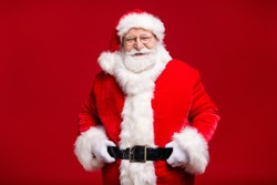 Photo of retired old man grey beard hand hip cheerful self-assured wait last days before newyear wear santa costume leather belt gloves coat spectacles headwear isolated red color background