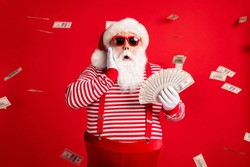 Photo of retired old man grey beard hold cash fan hand cheek shock money wear santa x-mas costume suspenders sunglass gloves striped shirt cap isolated red color background