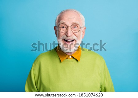 Photo of retired old man open mouth shiny smile excited wear glasses green pullover isolated blue color background