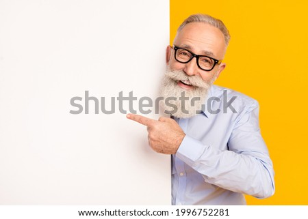 Photo of retired old man retired businessman point finger empty space banner wear glasses isolated on yellow color background