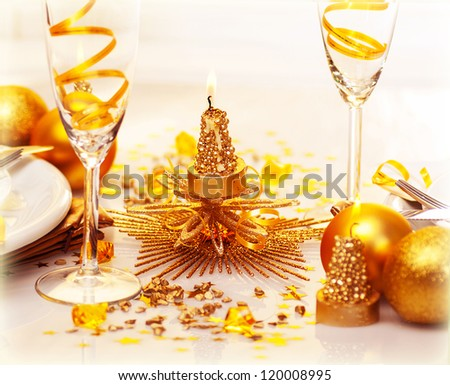 Photo of romantic Christmas dinner, two glasses for champagne adorned with golden ribbon, beautiful little candle, gold shiny bauble, holiday table setting, New Year decorations