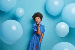 Photo of romantic curly haired woman blows kiss to lover, has party mood, dressed in pretty dress, poses against studio wall with balloons. Blue color prevails. Female enjoys her birthday party