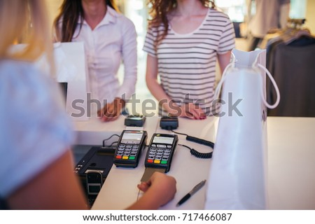 Photo of saleswoman pulling out the credit car from a credit card reader in the store.