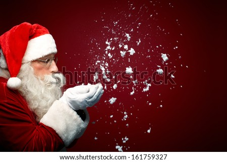 Photo of Santa Claus blowing snow and looking at it