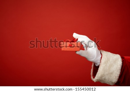 Photo of Santa Claus gloved hand holding small red giftbox