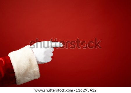 Photo of Santa Claus gloved hand in pointing gesture - stock photo