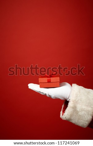 Photo of Santa Claus gloved hand with small red giftbox