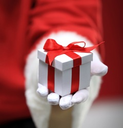 Photo of Santa Claus gloved hands holding white giftbox