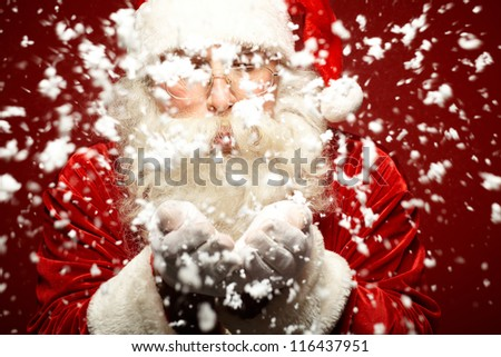Photo of Santa Claus in eyeglasses blowing snow from his palms