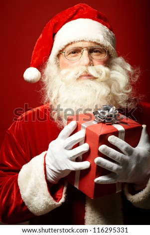 Photo of Santa Claus with red giftbox looking at camera