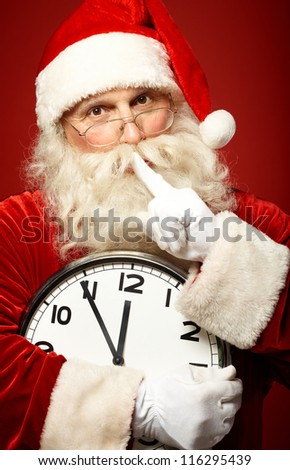 Photo of Santa holding clock showing five minutes to midnight and making shhh gesture