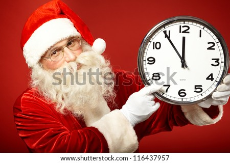 Photo of Santa pointing at clock showing five minutes to midnight
