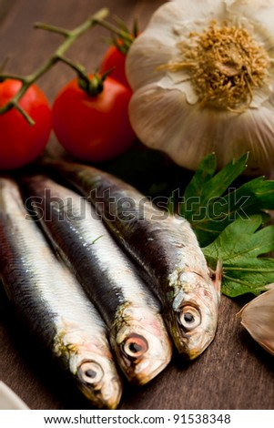 photo of sardines and different ingredients ready to be processed on wooden table