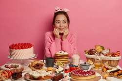 Photo of satisfied Asian woman sits at table overloaded with many desserts, breaks diet, has unhealthy nutrition, eats homemade cakes, croissants, dreams about eating sweets and not putting weight