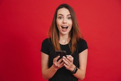 Photo of satisfied woman in black clothing looking on camera while using cell phone with joy over red background
