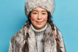 Photo of satisfied young siberia woman with two pigtails rosy cheeks smiles pleasantly at camera dresses for cold polar weather conditions isolated over blue background. Winter time concept.