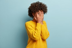 Photo of scared ethnic woman peeks through fingers, hides face, afraids of seeing something terrible, has Afro haircut, wears yellow clothes, isolated over blue wall. Omg, I dont want to see it