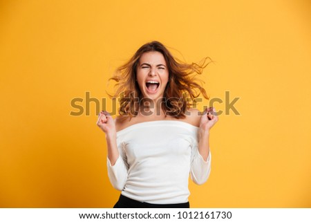 Photo of screaming young woman isolated over yellow background. Eyes closed.