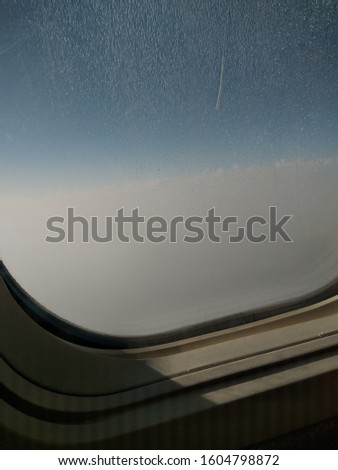 Photo of seeing outside from plane window, trying to see clouds.