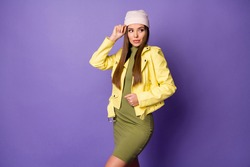 Photo of self-confident lady touch head cool hat look side empty space cunning sly eyes wear casual trend yellow leather jacket cap dress isolated pastel purple color background