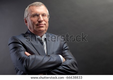 Photo of senior employer looking at camera on black background