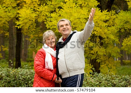 Photo of senior man showing something to his wife during walk in autumn forest
