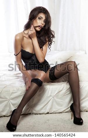 Photo of sensual beautiful brunette woman sitting on bed wearing elegant black lingerie.