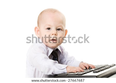 Photo of serious baby typing on keyboard and looking at camera