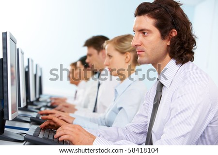 Photo of serious businesspeople typing and looking at monitors in line