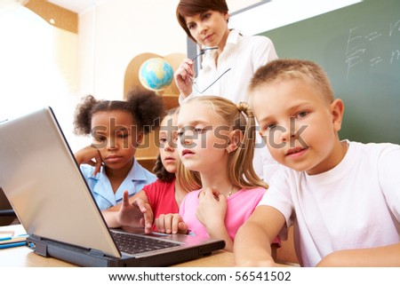 Photo of serious classmates and teacher looking at the laptop