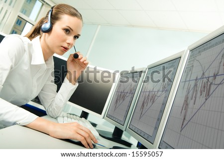 Photo of serious customer service representative sitting before computer while consulting someone in the office