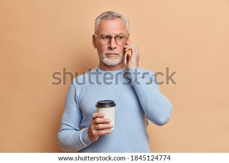 Photo of serious handsome bearded man has telephone conversation keeps smartphone near ear enjoys coffee break looks away wears transparent glasses and jumper isolated over brown background. Photo stock ©