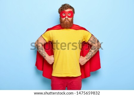 Photo of serious male in superhero costume, keeps hands on waist, possesses extraordinary talents, ready to protect our universe, isolated on blue wall. Bearded guy in red mask, cape, yellow t shirt Stockfoto ©