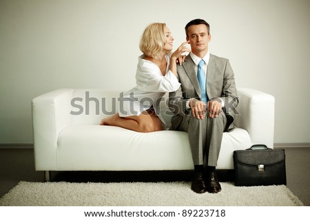Photo of serious man sitting on sofa with seductive woman teasing him