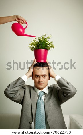 Photo of serious man with plant on head being watered from watering pot