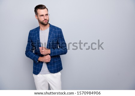 Photo of serious pensive pondering man fastening buttons on sleeves looking pensively into empty space in white pants spectacles isolated grey color background