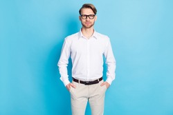 Photo of serious young man hold hands pockets wear glasses formalwear isolated on blue color background