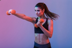 Photo of serious young sports woman make exercises with dumbbells isolated over purple wall background. Looking aside.
