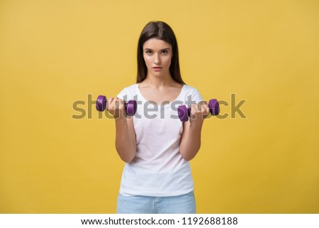 Stock Photo Photo of serious young sports woman make exercises with dumbbells isolated over yellow wall background.