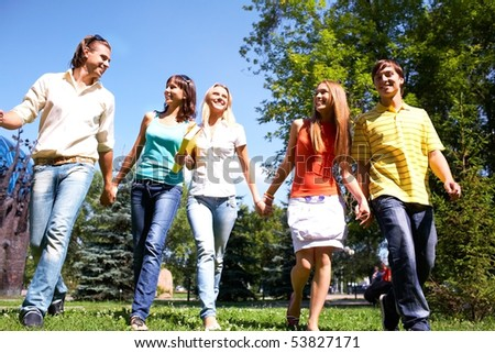 Photo of several happy friends walking in park and chatting