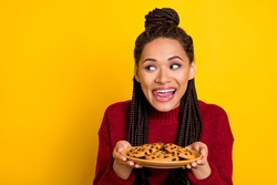 Photo of shiny sweet dark skin woman dressed sweater holding plate cookies empty space licking lips isolated yellow color background