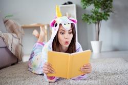 Photo of shocked excited surprised childish lady lay floor read interesting book wear cozy unicorn kigurumi indoors