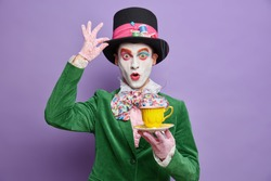 Photo of shocked mad hatter being on tea party wears big hat lace gloves and green costume poses with beverage has professional bright makeup isolated on purple background. Halloween carnival
