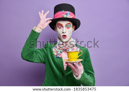 Photo of shocked mad hatter being on tea party wears big hat lace gloves and green costume poses with beverage has professional bright makeup isolated on purple background. Halloween carnival Photo stock ©