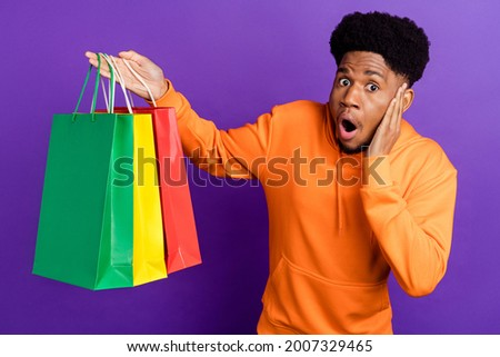 Photo of shocked young dark skin man hold hand cheek bags shop wear sweater isolated on purple color background Сток-фото ©
